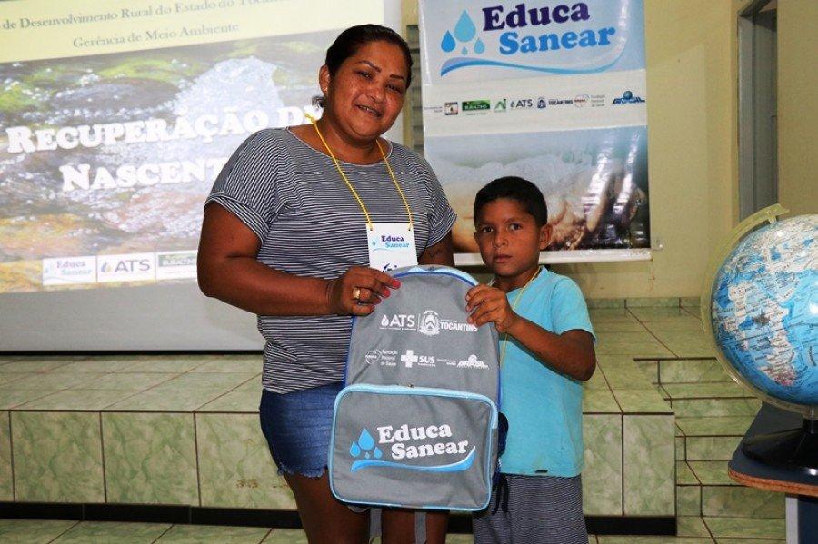 A dona de casa Nubia Guedes e o seu filho Leandro recebem kit educativo do Educa Sanear (Foto: Lidiane Moreira)