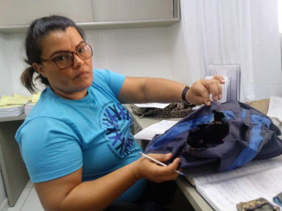 Valdeani mostra o estrago que o eletrônico fez na mochila (Foto: Josseli Carvalho)